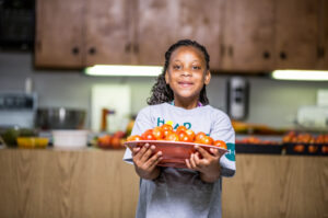 4-Her holding a bowl of tomatoes